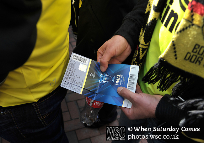 Bayern Munich 2 Borussia Dortmund 1, 25/05/2013. Wembley Stadium, Champions League Final. The first all-German Champions League final pitched Bayern, dominent domestically all season, against a Dortmund team who have troubled them so often in recent years. A Dortmund fan shows off two precious tickets. Photo by Simon Gill.
