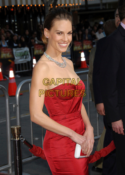 "HILARY SWANK .The Warner Brothers' Pictures L.A. Premiere of ""The Reaping"" held at The Mann Village Theatre in Westwood, California, USA..March 29th, 2007.half length red strapless dress belt diamond necklace white clutch purse  .CAP/DVS.©Debbie VanStory/Capital Pictures"
