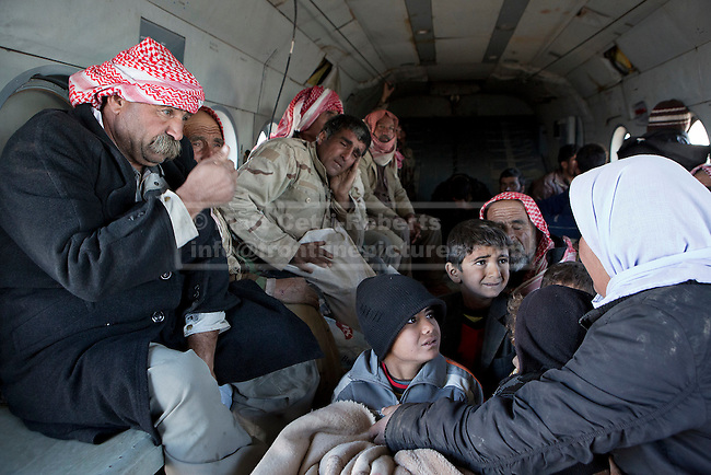 11/12/2014. Sinjar Mountains, Iraq. Yazidi refugee children look at their mother as they, and other Yazidis, are evacuated from Mount Sinjar.<br /> <br /> Although a well publicised exodus of Yazidi refugees took place from Mount Sinjar in August 2014 many still remain on top of the 75 km long ridge-line, with estimates varying from 2000-8000 people, after a corridor kept open by Syrian-Kurdish YPG fighters collapsed during an Islamic State offensive. The mountain is now surrounded on all sides with winter closing in, the only chance of escape or supply being by Iraqi Air Force helicopters.