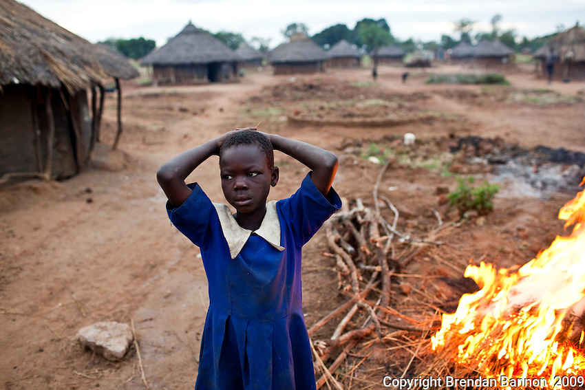 A Ugandan school girl passing a crop burn enroute to school.