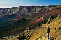 Lone male tourist enjoying the early morning light on the colorful cinder cones in HALEAKALA NATIONAL PARK on Maui in Hawaii USA