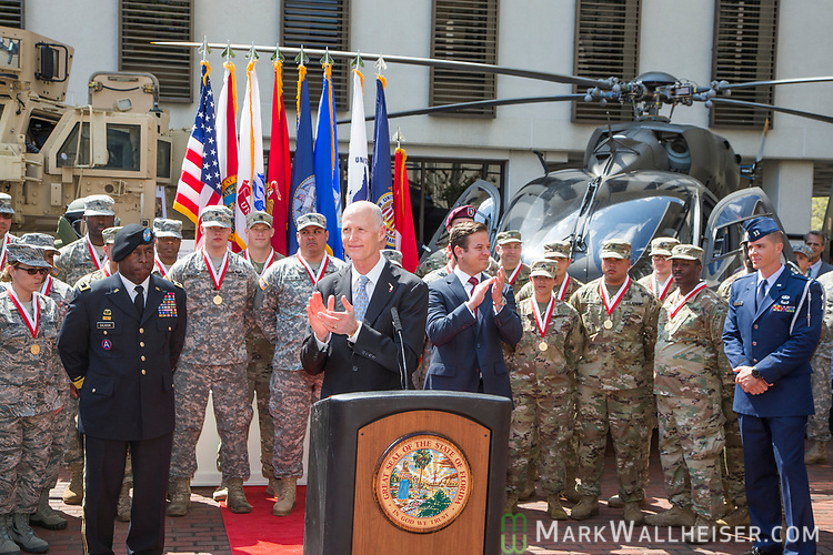 """Florida Governor Rick Scott and Lt. Gov. Carlos Lopez-Cantera applaud during the Florida Department of Military Affairs and the Florida National Guard sponsored """"Florida National Guard Day"""" at the Capitol"""