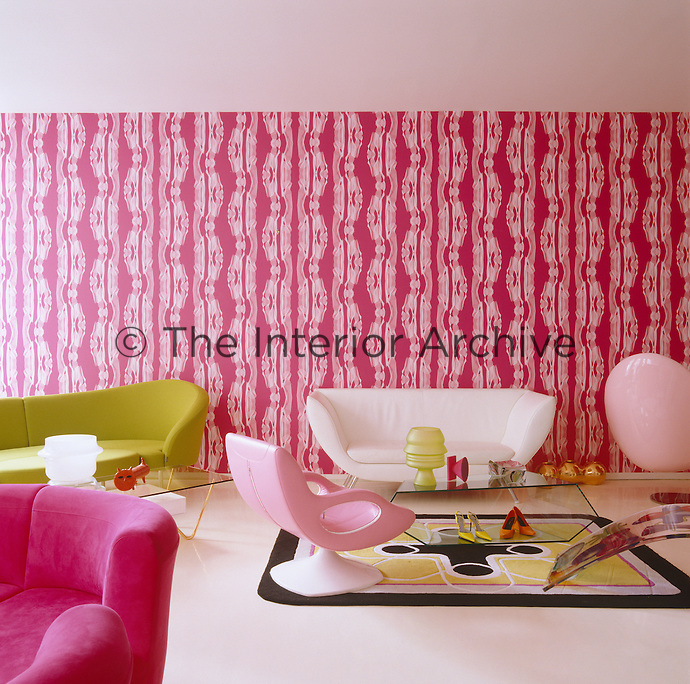 The curved sofas and chairs in the living room are designed by Karim Rashid as is the pink and white wallpaper which serves as a backdrop