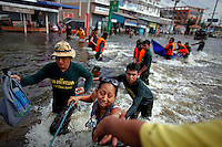 Thai soldiers help residents crossing the strong stream of floodwaters in Pathum Thani province October 14, 2011. Thai Prime Minister Yingluck Shinawatra tried to reassure residents of Bangkok on Friday that the capital should largely escape the flooding that has covered a third of the country since July and caused damage of at least $3 billion. REUTERS/Damir Sagolj (THAILAND)