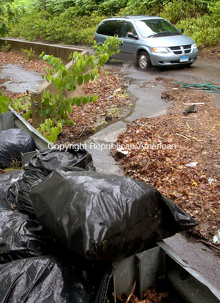 WATERBURY CT. 01 June 2015-060115SV02-A car makes its way up Waterville Street in Waterbury Monday. Waterville Street is a one-way road created by Hychko Co. and has become a dump zone. <br /> Steven Valenti Republican-American