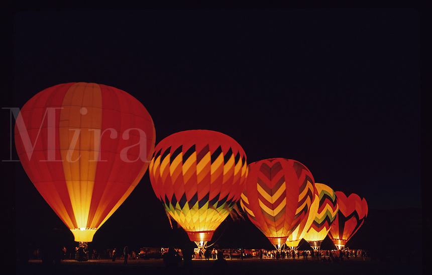 Hot air balloons illuminated at night.
