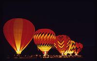 Hot air balloons illuminated at night.