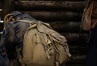 A mannequin dressed as a soldier in blue uniform with a beige backpack, hiding his head in his hands. At a War Museum in Europe.