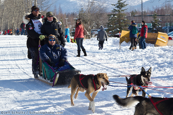 Aaron Peck and team run past spectators on the bike/ski trail during the Anchorage ceremonial start during the 2013 Iditarod race.    Photo by Britt Coon/IditarodPhotos.com