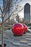 Giant Christmas ornaments at the Klyde Warren Park with the city skyline in the background.