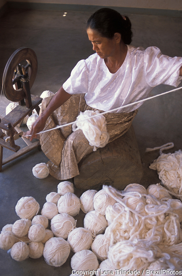 Handicraft woman using a loom for making cotton thread that will be used to produce bedspreads, towels, hammocks and blankets. Berilo city at Vale do Jequitinhonha in Minas Gerais State, Brazil.