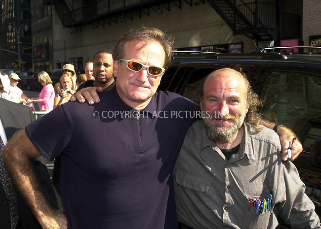 """Actor and funnyman Robin Williams arrives at Ed Sullivan Theater for the taping of the """"Late Show With David Letterman."""" Robin is pictured with a homeless autograph seeker known as """"Radioman."""" Their similarities are striking. Could it be that they were separated at birth? New York, August 20, 2002. REF: PVUS2067. Please byline: Peter Vail/NY Photo Press.   ..*PAY-PER-USE*      ....NY Photo Press:  ..phone (646) 267-6913;   ..e-mail: info@nyphotopress.com"""
