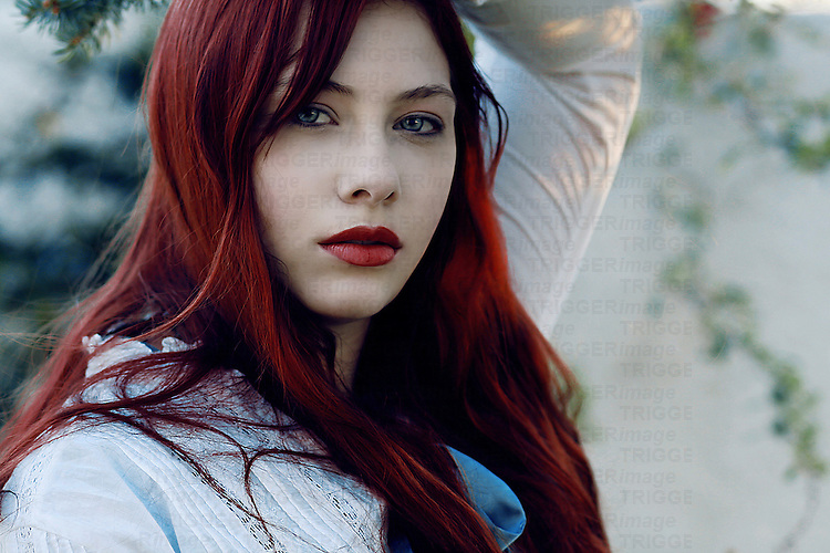 A close up of a girl with red hair looking at camera