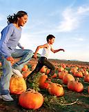 USA, California, happy girl and boy running in the pumpkins at Bob's Pumpkin Patch, Half Moon Bay