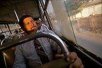 Iraldo Alves de Oliveira peers from a city bus window as he commutes across town to make a guest sermon at a related Assembly of God church. Oliveira is in high demand as a speaker and example of religious and familial success.