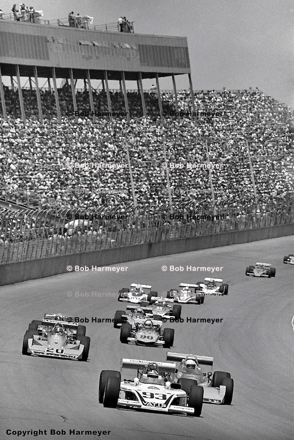 The field races past the grandstand during the 1976 USAC Champ Car event at Michigan International Speedway.