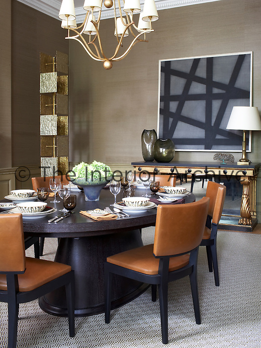 A large oval table is laid for lunch in this contemporary dining room decorated with modern art