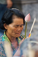 Thai woman offering Lotus flower and incense to Buddha.  Lotus flower is symbol of enlightenment and incense represents pure moral conduct,.Wa Phra That Doi Suthep Rajvoravihara, Chiang Mai, Thailand