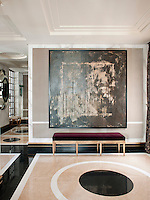 The entrance hallway of a stylish apartment. Walls covered in marbleised hand painted paper and a polished floor creates an atmosphere where classic and modern elements coexist comfortably in a totally contemporary space.