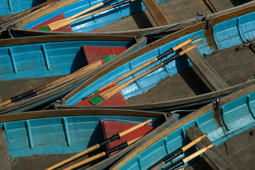 Blue skiffs at their mooring on the Cherwel River by Magdalen Bridge, Oxford, England