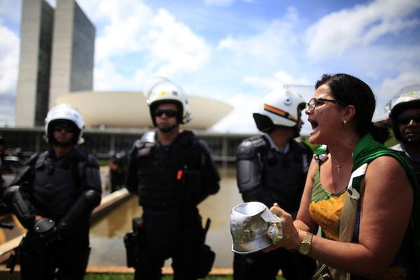 BRA515. BRASILIA (BRASIL), 15/03/2015.- Una mujer grita consignas frente a una fila de policías durante una manifestación contra la presidenta brasileña, Dilma Rousseff, hoy, domingo 15 de marzo de 2015, en la ciudad de Brasilia (Brasil). Cientos de miles de personas protestaron contra la presidenta Dilma Rousseff, en Brasilia, en el marco de una jornada de manifestaciones convocadas en decenas de ciudades de todo el país. La protesta de Brasilia comenzó a las 9.30 hora local (12.30 GMT) en la explanada de los ministerios y llegó hasta la frente del Congreso Nacional Brasileño, con la participación de grupos de ciudadanos opositores sin vínculo declarado con partidos políticos. Los manifestantes corearon consignas contra Rousseff y el oficialista Partido de los Trabajadores (PT) y en rechazo de la corrupción. EFE/Fernando Bizerra Jr.