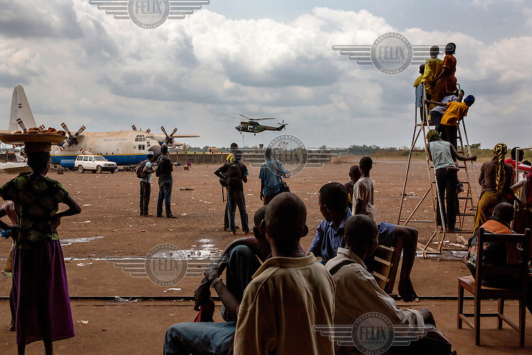 A helicopter lands at M'Poko International Airport watched by a group of Muslims waiting for evacuation from  as a  In 2013 a rebellion by a predominantly Muslim rebel group Seleka, led by Michel Djotodia, toppled the government of President Francios Bozize. Djotodia declared that Seleka would be disbanded but as law and order collapsed the ex-Seleka fighters roamed the country committing atrocities against the civilian population. In response a vigillante group, calling themselves Anti-Balaka (Anti-Machete), sought to defend their lives and property but they then began to take reprisals against the Muslim population and the conflict became increasingly sectarian. French and Chadian peacekeeping forces have struggled to contain the situation and the smaller Muslim population began to flee the country.
