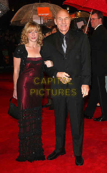 PATRICK STEWART & GUEST.The 2006 Orange British Academy Film Awards, Odeon Leicester Square, London, UK..February 19th, 2006.Ref: BEL.full length black suit dress burgundy satin arms linked bafta baftas.www.capitalpictures.com.sales@capitalpictures.com.© Capital Pictures.