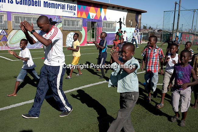 Khayelitsha, South Africa March 11, 2013: Luyanda Hans, a Senior leader, holds a skills training session at Amandla EduFootball which was founded by Jakob Schlichti and Florian Zech in the field in Khayelitsha a poor township outside Cape Town, South Africa. They use football to initiate, support educational projects for youth in the township. The program keep children busy and it decreases the risk of them joining gang, criminal activity or teenage pregnancy. The crime level has decreased substantially in the area since the program was created in 2006. (Photo by: Per-Anders Pettersson
