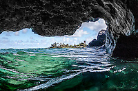 Looking out at the bay and coastline from the inside of sea cave at Waimea Bay, North Shore, O'ahu.