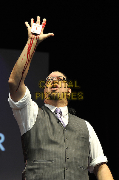 Penn Jillette .Penn and Teller performing 'Conversations with Penn and Teller - 35 Years of Magic and Bulls'%+t', indigo2, Greenwich, London, England. .7th December 2011.bullshit stage concert performing performance half length grey gray waistcoat white shirt pinstripe knife dagger hand profile card stab stabbing blood arm in air .CAP/MAR.© Martin Harris/Capital Pictures.