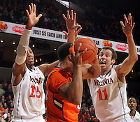 Virginia forward Akil Mitchell (25) and Virginia forward Evan Nolte (11) double team Clemson forward/center Devin Booker (31) during the game Thursday in Charlottesville, VA.