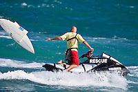 The lifeguard drops a broken board back on the shore line, North Shore of Oahu, Hawaii. Photo: joliphotos.com