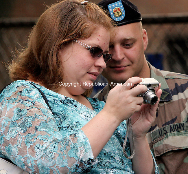 WATERBURY, CT-20June 2006-062006TK03- Melissa and Sgt. Chris Couture of Bristol preview snap shots taken befor the departure of the 143 Combat Sustain Support Battalion. Tom Kabelka Republican-American (Melissa and Sgt. Chris Couture)