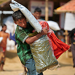 A Rohingya boy carries a tarp, blankets and other items that he received from Christian Aid in the Jamtoli Refugee Camp near Cox's Bazar, Bangladesh. Christian Aid is a member of the ACT Alliance.<br /> <br /> More than 600,000 Rohingya have fled government-sanctioned violence in Myanmar for safety in Bangladesh.