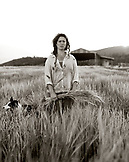 USA, California, woman standing with crops in field (B&W)