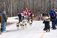 Rob Cooke and team run past spectators on the bike/ski trail with an Iditarider in the basket during the Anchorage, Alaska ceremonial start of the 2015 Iditarod race. Photo by Ed Bennett/IditarodPhotos.com