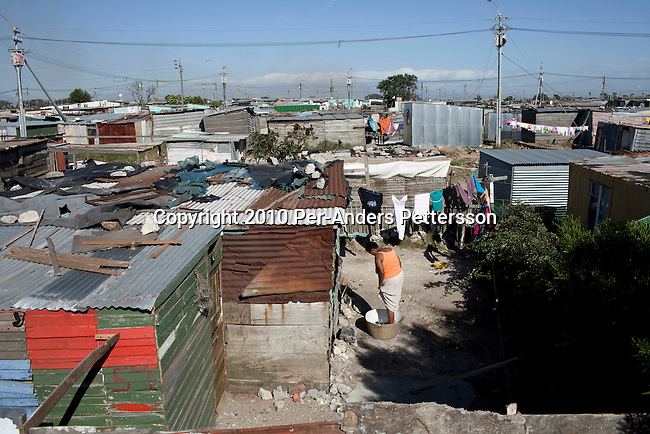 GUGULETU, SOUTH AFRICA - DECEMBER 14: A unidentified woman washes her laundry outside her tin shack on December 14, 2010, In the Barcelona section of Guguletu, a township outside Cape Town, South Africa. Guguletu is one of the biggest black townships in Cape Town and it was here where where British honeymooners Anni Dewani, 28, and Shrien Dewani, 31, were attacked. Anni Dewani was found with bullets in her chest in the back of the taxi after the newly weds were ambushed whilst traveling near a notorious settlement known as Barcelona. (Photo by Per-Anders Pettersson/Getty Images)