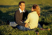 Couple sitting in field of grass, Mt. Tamalpais, N. California