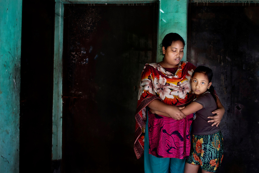 Laboni Akhter, right, holds her aunt Rupali, in front of the site of her mother Dulali's (21) death. Dulali died in the factory fire at Tazreen Fashions, in Ashulia, Bangladesh, when the fire engulfed surrounding buildings.