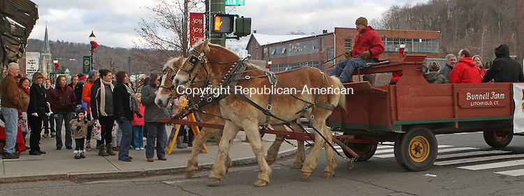 Winsted, CT-120713MK21 Rick Bunnell, from Bunnell Farm in Litchfield, drives the horse drawn wagon during Main Street Christmas festivities in Winsted on Saturday afternoon. Over a hundred locals toured the sidewalk along Main Street to enjoy horse-drawn hay rides, the roasting of marshmallows with local firefighters, pictures with Santa and the Christmas Tree lighting at East End Park. The event will also included hot chocolate, popcorn, cookies, carol singing, crafts and storytelling. Tricia Twomey, director of the parks and recreation department, said that this was the fifth year for the festival sponsored by Friends of Main Street and was supported by various local businesses.