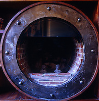 A circular brick fireplace with a riveted metal frame stands at one end of a small study