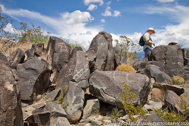 A visitor explores among the petroglyphs at Three Rivers State Park near Tularosa