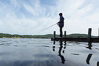 Hortonia, VT, USA - August 24, 2011: Girl fishing from jetty in lake, low level view