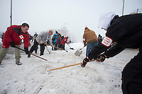 Volunteers shovel snow back onto the track at the ceremonial start of the Iditarod sled dog race Anchorage Saturday, March 2, 2013. ..Photo (C) Jeff Schultz/IditarodPhotos.com  Do not reproduce without permission