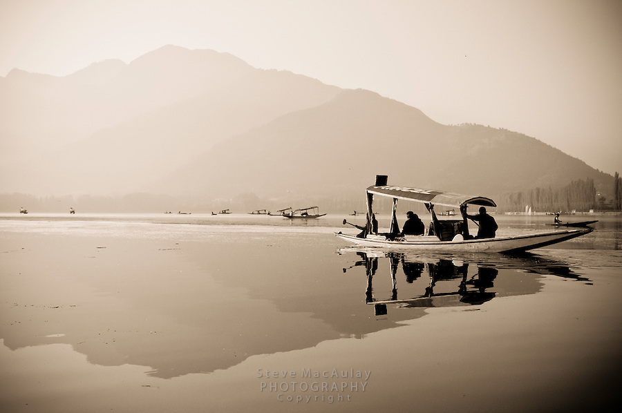 Toned black and white photograph of traditional Kashmiri shikara on Dal Lake at sunrise, Srinagar, Kashmir, India.