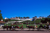 HORSE-DRAWN CARRIAGE TRAFFIC ON THE STREETS OF MACKINAC ISLAND, MICHIGAN BELOW FORT MACKINAC IN BACKGROUND.