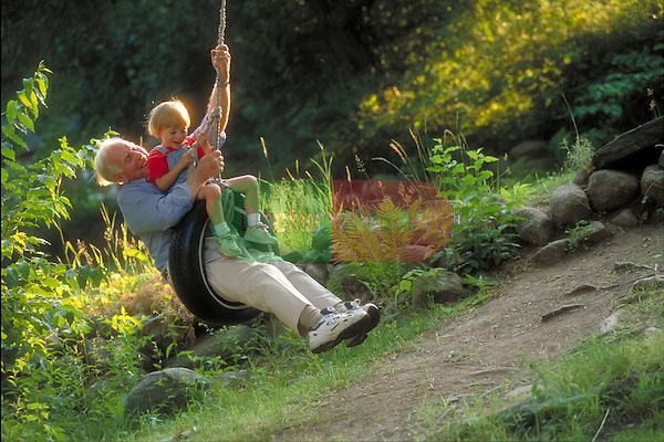 grandfather swinging in tire-swing with young grandson