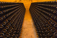 In the underground winecellar that is an old chalk quarry: thousands and millions of bottles aging, these one are standing in racks (pupitres) awaiting disgorgement, Champagne Ruinart, Reims, Champagne, Marne, Ardennes, France, low light grainy grain