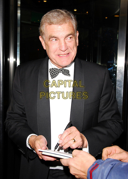 SIR TREVOR BROOKING.The SPARKS Winter Ball, London Hilton, Park Lane, London, UK..December 14th, 2006.half length black tuxedo jacket bow tie signing autograph.CAP/CAN.©Can Nguyen/Capital Pictures