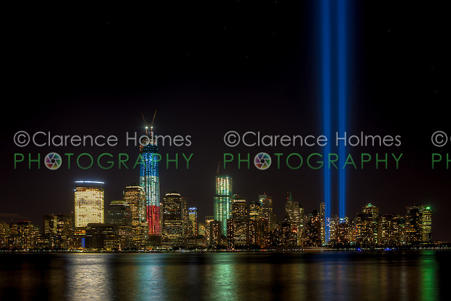 The twin beams of light of the Tribute in Light, an annual memorial to the events of September 11, 2001, shine into the evening sky in New York City over the skyline of lower Manhattan during testing on Monday, September 10, 2012.  This view of the skyline includes the Freedom Tower (One World Trade Center), under construction at the site of the original Twin Towers.  The Freedom Tower, lighted in the red, white, and blue colors of the American flag, is scheduled for completion in 2013.